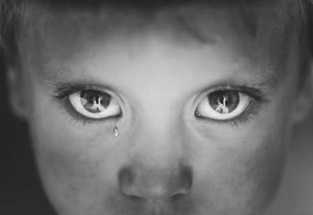black person: the eyes of a little boy with a tear