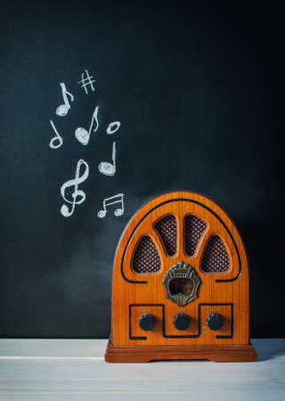 shortwave: Retro Radio on a dark background with musical notes on a blackboard Stock Photo