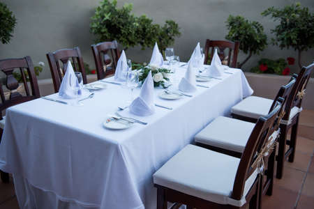 festively: Festively laid table with white tablecloths with glasses and plates Stock Photo