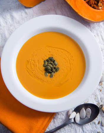 Autumn pumpkin soup on a light background