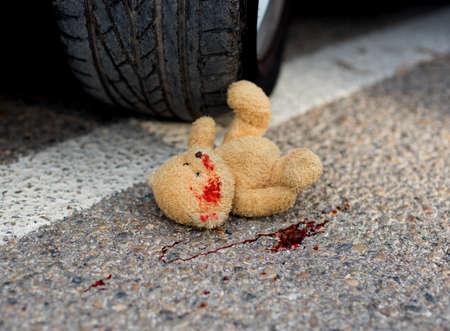 자동차 바퀴 밑의 피에 부드러운 장난감 곰 스톡 콘텐츠