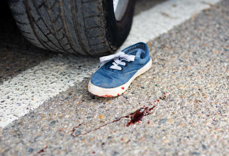 children's shoes in the blood under the car wheels