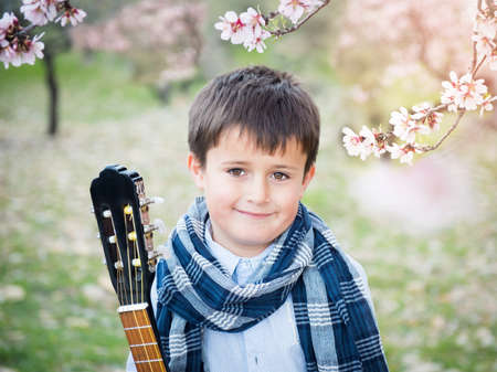 Young handsome boy in blooming gardens with a guitar