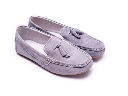 children s feet: Moccasins of suede on a white background
