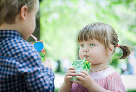 Young children drink juice photo