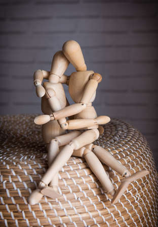 tenderly: Two Lovers wooden man tenderly cuddling indoors Stock Photo