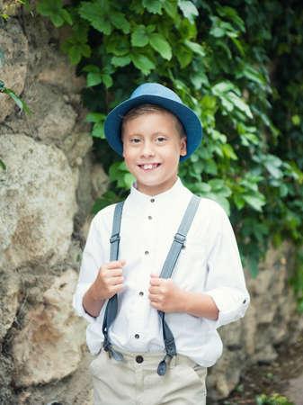 Portrait of happy joyful beautiful stylish little boy in hat photo