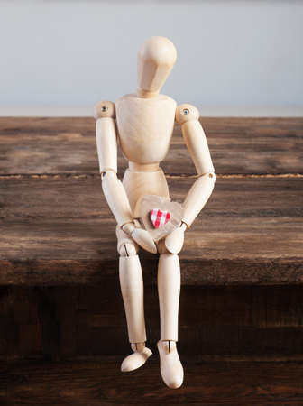 marioneta de madera: Wooden doll with heart in hands sitting on a wooden table.