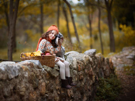 ittle: ittle girl with big dog in the forest in autumn Stock Photo