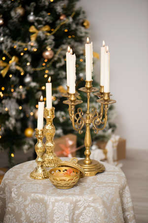 candles and sweets on the New Years table. Christmas tree with lanterns in the background Stock Photo