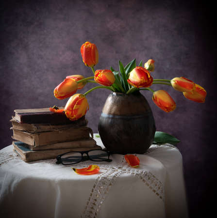 still life with old books and tulips in a dark vase 写真素材
