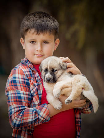 Handsome little boy is holding a dog. Close-up portrait