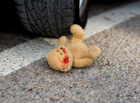 soft toy bear in the blood under the car wheels 版權商用圖片