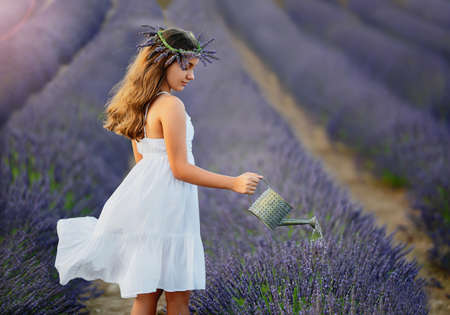 Beautiful girl with a wreath of lavender flowers on her head