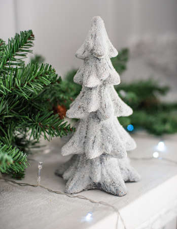 Small white beautiful decorative Christmas tree on new Year background.