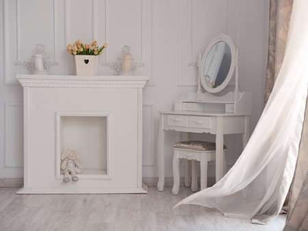 Beautiful white room with fireplace and table with mirror. Imagens