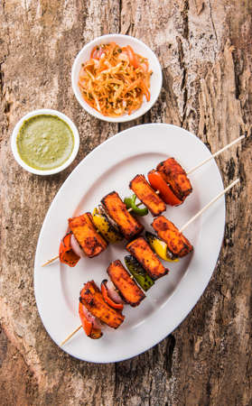 kabab: Paneer Tikka Kabab - Tandoori Indian cheese skewers, malai paneer tikka  malai paneer kabab, chilli paneer served in white plate with barbecue stick and colourful capsicum and onion, with green sauce