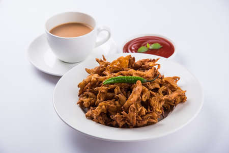 onion bhaji: Crispy onion bhaji or kanda bhaji or fried onion pakore or pakode, delicious street food, favourite indian snack in monsoon served with hot tea