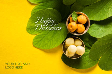 indian festival dussehra, showing golden leaf with traditional indian sweets pedha in silver bowl, Dussehra greeting card Banque d'images