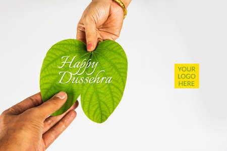 indische Fest Dussehra, zeigt goldene Blatt mit traditionellen indischen Süßigkeiten pedha in Silberschale, Dussehra Grußkarte