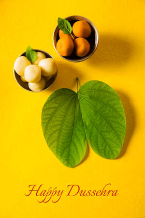 indian festival dussehra, showing golden leaf with traditional indian sweets pedha in silver bowl, Dussehra greeting card 写真素材