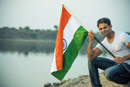indian young man holding and waving indian flag, conceptual image for republic day or independence day, handsome man holding flag, man holding indian flag, indian flag waving Stock Photo