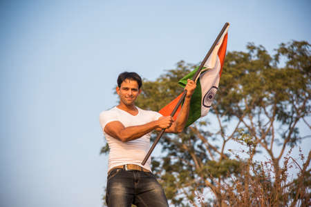 30 years old man: indian young man holding and waving indian flag, conceptual image for republic day or independence day, handsome man holding flag, man holding indian flag, indian flag waving Stock Photo