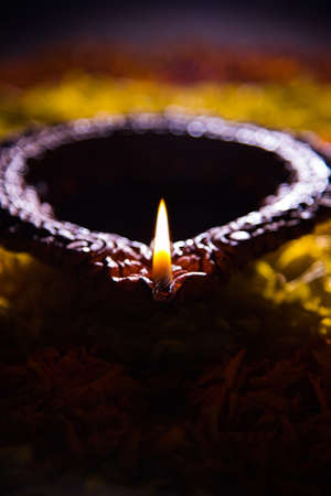 panti: Traditional diya or oil lamp lit on colorful rangoli made up of marigold flower petal, on the festival of lights called diwali or deepawali, selective focus Stock Photo