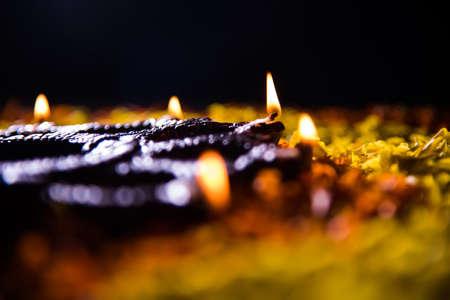 panti: Traditional diya or oil lamp lit on colorful rangoli made up of marigold flower petal, on the festival of lights called diwali or deepawali, selective focus Stock Photo