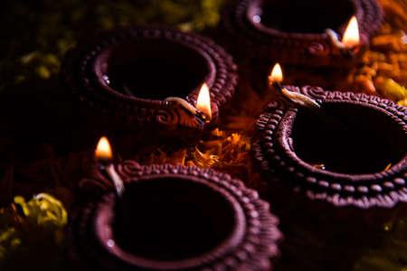 rangoli: Traditional diya or oil lamp lit on colorful rangoli made up of marigold flower petal, on the festival of lights called diwali or deepawali, selective focus Stock Photo
