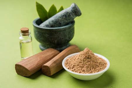 Chandan or sandalwood powder with traditional mortar, sandalwood sticks, perfume or oil and green leaves. selective focus 版權商用圖片