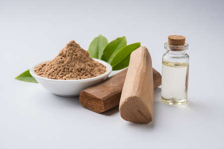 Chandan or sandalwood powder with traditional mortar, sandalwood sticks, perfume or oil and green leaves. selective focus Archivio Fotografico