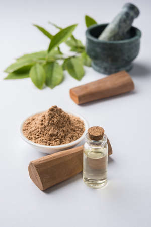 Chandan or sandalwood powder with traditional mortar, sandalwood sticks, perfume or oil and green leaves. selective focus Banco de Imagens