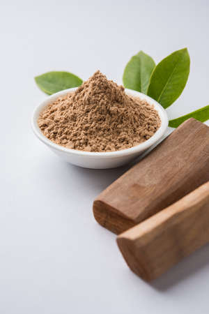 Chandan or sandalwood powder with traditional mortar, sandalwood sticks, perfume or oil and green leaves. selective focus Фото со стока