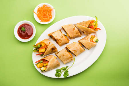Indian popular snack food called Vegetable spring rolls or veg roll or veg franky or veg wrap made using paneer or cottage cheese and vegetables wrapped inside parathachapatiroti with tomato ketchup. Stock Photo