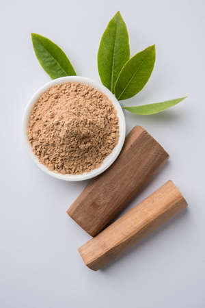 Chandan or sandalwood powder with traditional mortar, sandalwood sticks, perfume or oil and green leaves. selective focus Stockfoto