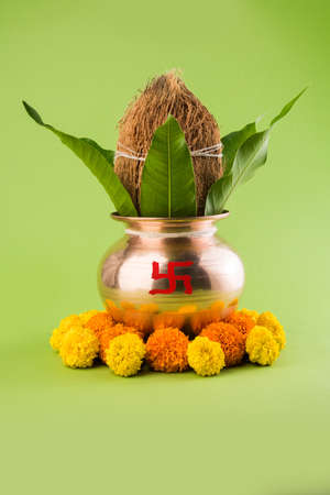 A copper puja kalash with coconut and mango leaf with floral decoration essential in Hindu Stock Photo
