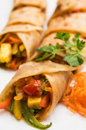 filled roll: Indian popular snack food called Vegetable spring rolls or veg roll or veg franky or veg wrap made using paneer or cottage cheese and vegetables wrapped inside parathachapatiroti with tomato ketchup. Stock Photo
