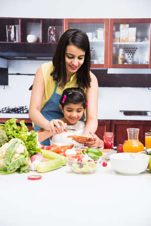 Pretty Indian young lady or mother with cute girl child or daughter in kitchen having fun time with table full of fresh vegetables and fruits Imagens