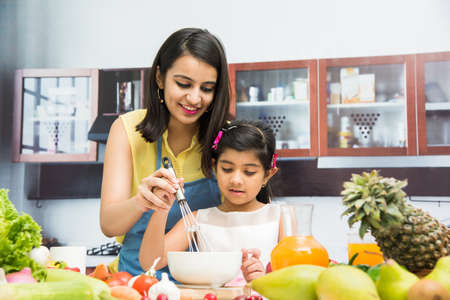 Pretty Indian young lady or mother with cute girl child or daughter in kitchen having fun time with table full of fresh vegetables and fruits Archivio Fotografico