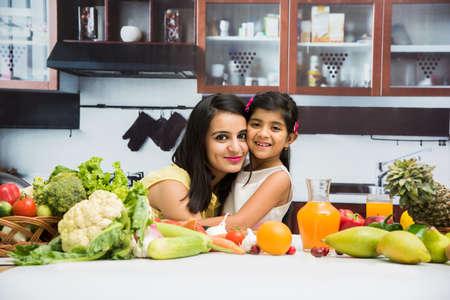 꽤 인도 젊은 아가씨 또는 어머니 귀여운 소녀 자식 또는 신선한 야채와 과일 가득한 테이블 재미 시간에 부엌에서 딸 스톡 콘텐츠