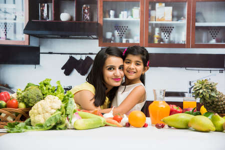 Pretty Indian young lady or mother with cute girl child or daughter in kitchen having fun time with table full of fresh vegetables and fruits Banque d'images