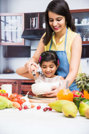 Pretty Indian young lady or mother with cute girl child or daughter in kitchen having fun time with table full of fresh vegetables and fruits 免版税图像