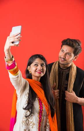 Indian Festival - Rakshabandhan or Raksha Bandhan Or Rakhi Festival also known as Narali Purnima and people, young sister tying traditional Rakhi Thread on brothers wrist or taking selfie picture or holding gifts