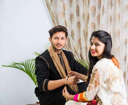 Festival indiano - Rakshabandhan o Raksha Bandhan Or Rakhi Festival conosciuto anche come Narali Purnima e la gente, giovane sorella che lega il tradizionale Rakhi Thread sul polso del fratello o che prende selfie immagine o regali Archivio Fotografico - 80400108
