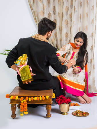 Indian Festival - Rakshabandhan or Raksha Bandhan Or Rakhi Festival also known as Narali Purnima and people, young sister tying traditional Rakhi Thread on brother's wrist or taking selfie picture or holding gifts Archivio Fotografico