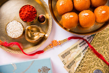 Rakhi gifts,  diya in a puja thali, indian currency notes, envelope and sweet motichur laddu Stock Photo