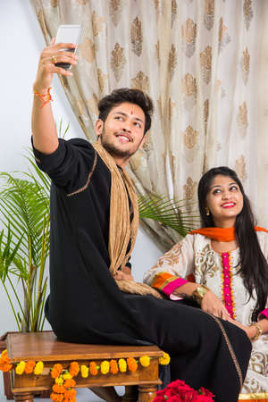 Indian Festival - Rakshabandhan or Raksha Bandhan Or Rakhi Festival also known as Narali Purnima and people, young sister tying traditional Rakhi Thread on brothers wrist or taking selfie picture or holding gifts