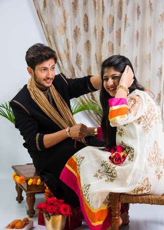 kurta: Indian Festival - Rakshabandhan or Raksha Bandhan Or Rakhi Festival also known as Narali Purnima and people, young sister tying traditional Rakhi Thread on brothers wrist or taking selfie picture or holding gifts