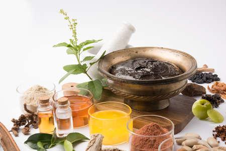 Chyawanprash, 인도 Ayurvecid 규정 식 보충 교재, 흰색 배경에 그것의 주위에 누워의 그릇의 상위 뷰.